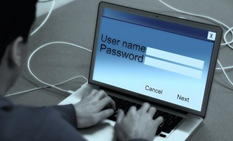 Persona utilizando un portátil mientras escribe usuario y contraseña
