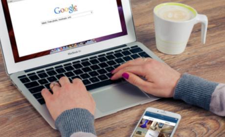 Mirando en el portátil Google con el móvil encendido