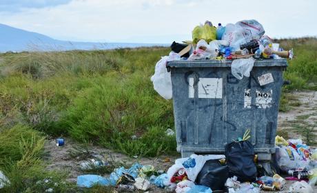 Contenedor con plástico y restos de basura