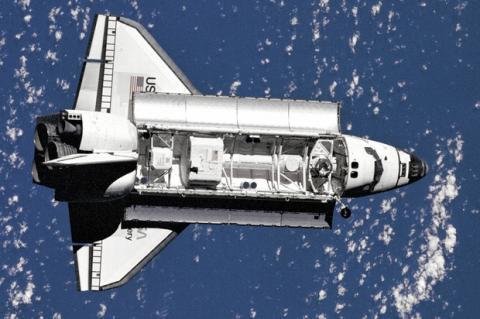 Transbordador espacial orbitando sobre la tierra