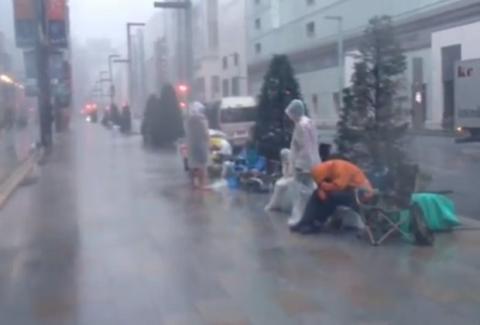 Fans de Apple siguen en fila en medio de un tifón