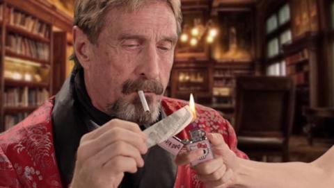 Imagen de John Mcafee encendiendo un cigarro con un billete