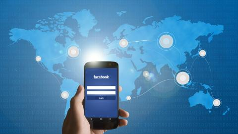 Móvil con Facebook y de fondo el mundo