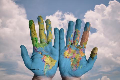 Manos pintadas con el mapa del mundo