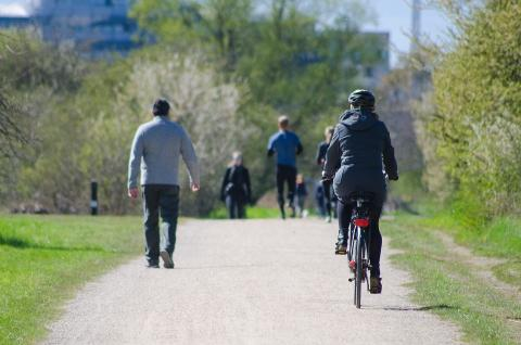 Un grupo de gente y una mujer en bicicleta en una vía verde