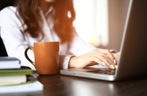Mujer trabajando en portátil con café