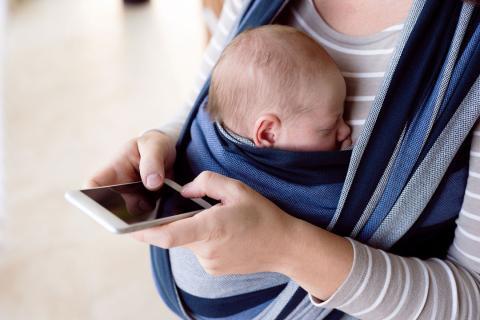 Una mamá que portea a su bebé consulta el móvil