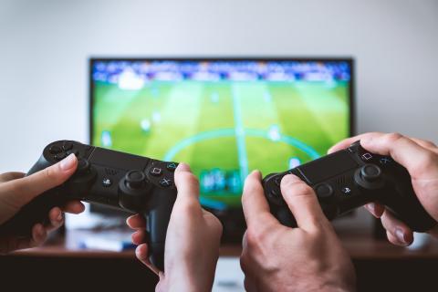 Dos personas con mandos de PS4 jugando a FIFA
