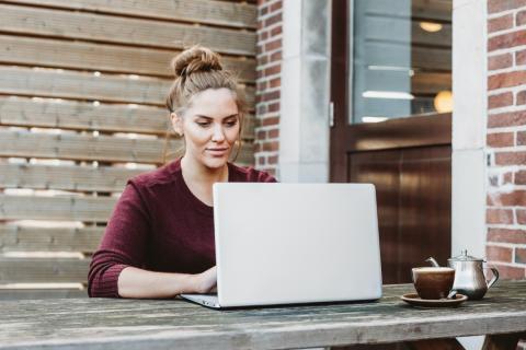 Mujer usando un portátil en una mesa y tomando un té