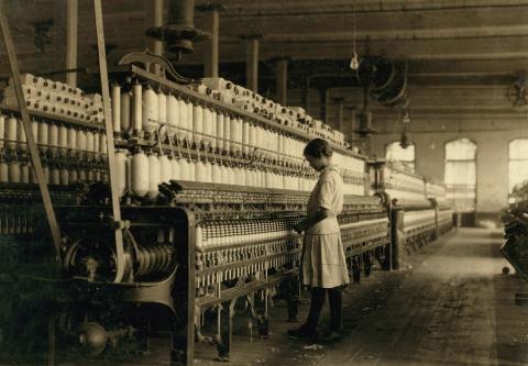 Una niña trabaja en una fábrica textil a principios del siglo XX
