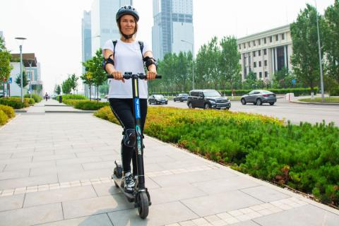 Mujer con casco montada en una scooter eléctrica