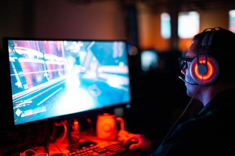 Gamer jugando en un ordenador con auriculares a un FPS