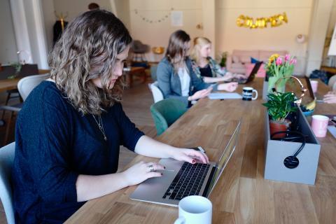 Una mujer usando un portátil en un coworking