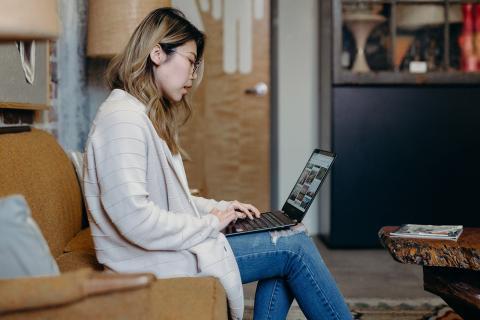 Mujer usando un portátil sobre sus piernas en un salón