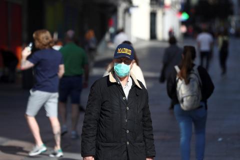 Un hombre camina por Madrid con mascarilla por temor la coronavirus