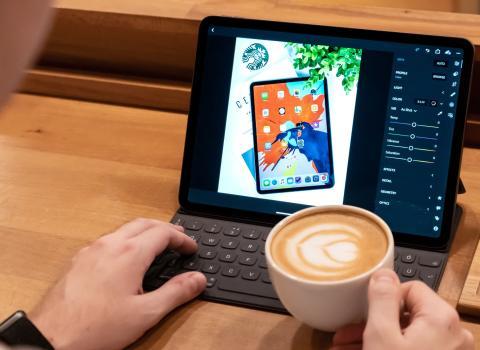 Hombre usando un iPad Pro con teclado físico y sujetando una taza con café