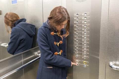 mujer boton ascensor