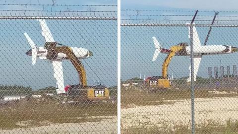 Avión Learjet sostenido por una excavadora