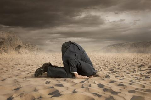Hombre escondiendo la cabeza en el suelo