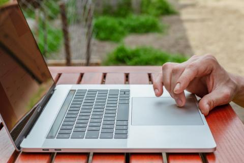 Mano tocando un portátil Apple MacBook Pro