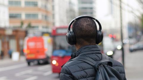 Hombre con auriculares inalámbricos en una ciudad