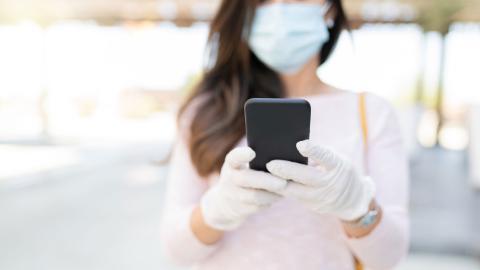 Mujer con mascarilla usando el móvil