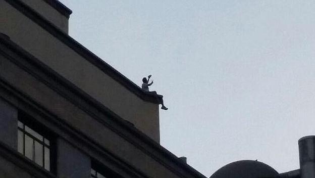Un joven se hace un peligroso selfie poniendo su vida en peligro a 30 metros de altura en la azotea de un edificio de Madrid.